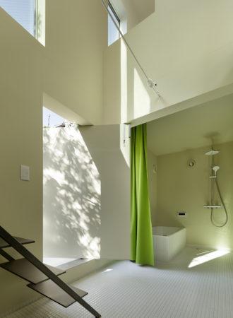 T邸浴室。回転扉が西側物干し場とつなげる。左の階段から2階テラスへ。